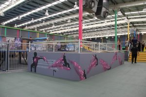 Airborne trampoline park interior decorated with urban graffiti and wall murals.