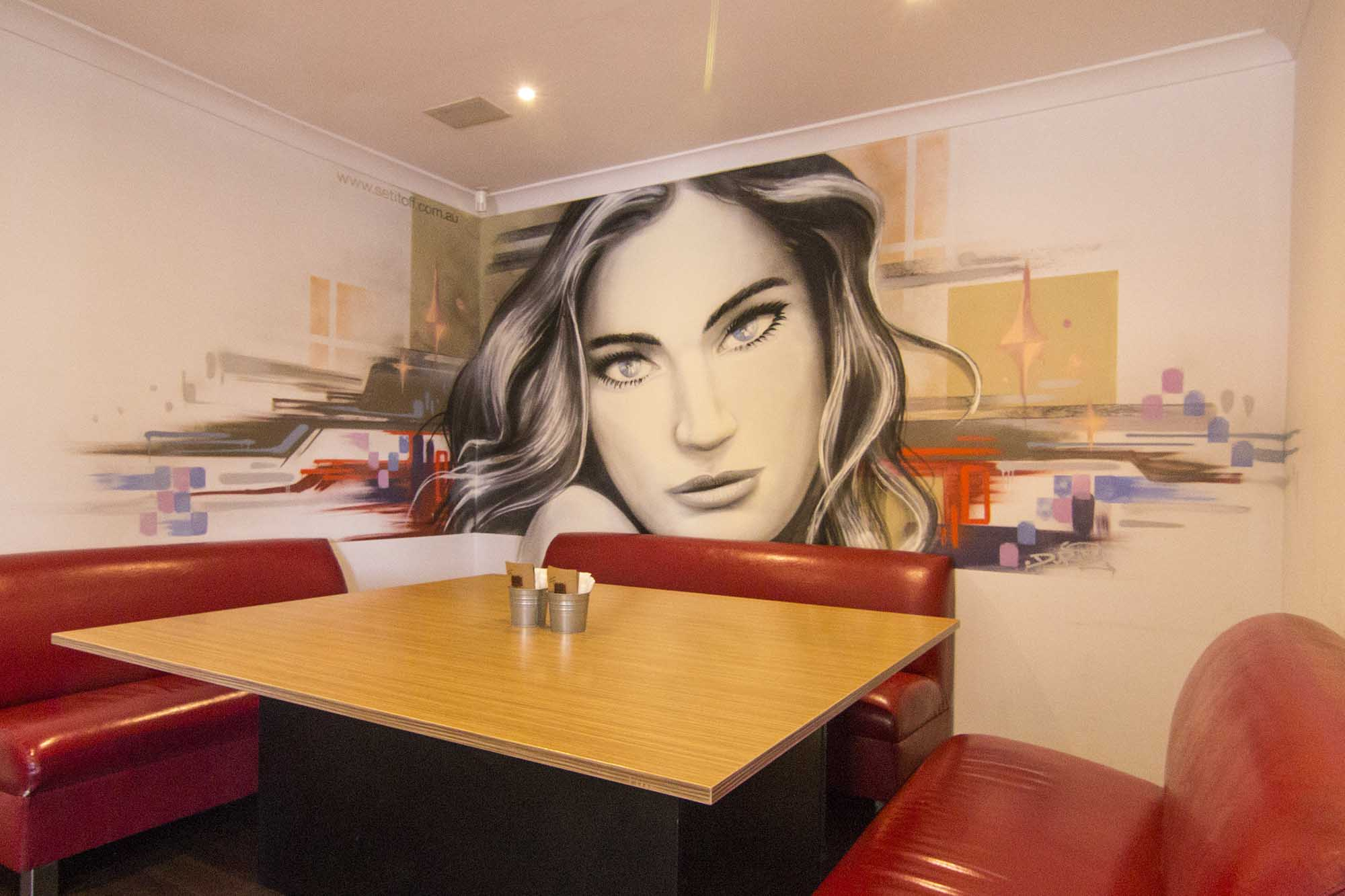 Graffiti mural portrait inside restaurant.