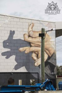 Shadow puppets large-scale photorealistic wall mural for outdoor entertainment area.