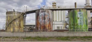 Old, industrial silos are restored with graffiti art representing the company that owns them.