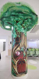 Enchanted tree mural on a pillar