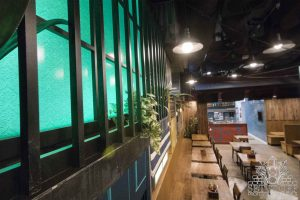 Continuous wall murals throughout a Vietnamese restaurant combined with other recycled materials and sculptures.