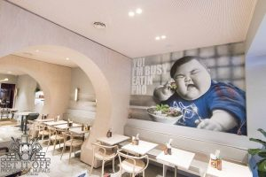 An interior wall mural based on the Yo I'm Busy Eating Pho meme in a restaurant.