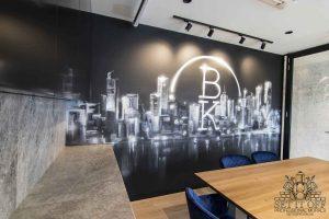 A monochromatic graffiti mural on office walls with company logo.