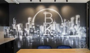 A monochromatic graffiti mural on office walls with company logo.