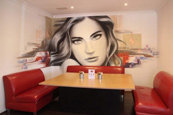 Graffiti mural portrait inside restaurant.