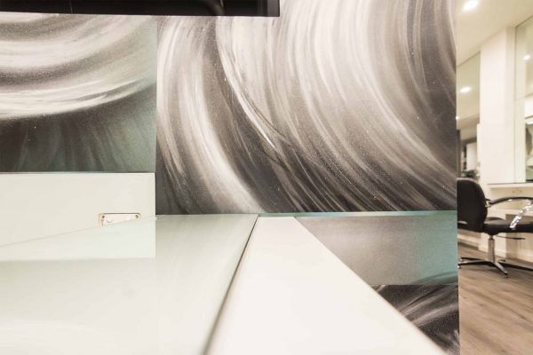 Interior of hair salon decorated with wall mural featuring textured strands of hair.